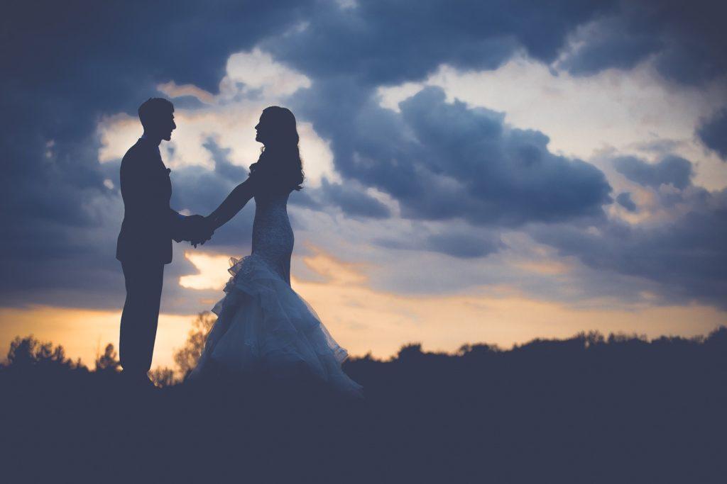 Noivo e noiva de mãos dadas com céu nublado ao fundo