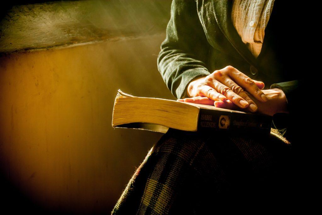 homem com as mãos em cima de livro