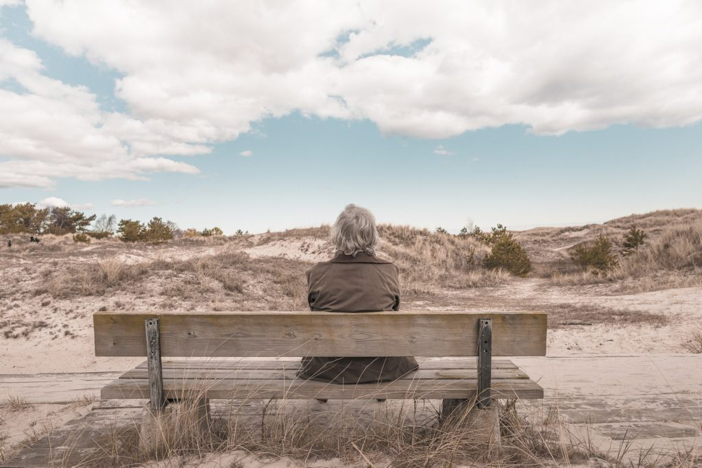 homem sentado no banco no deserto