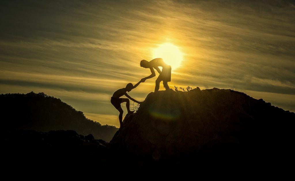 homens subindo montanha no por do sol